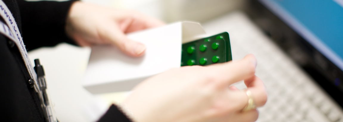 Pharmacist putting medication in a box